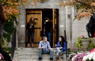 Photo of students sitting on the steps in front of a building
