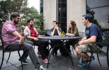 Photo of students sitting outside at a table